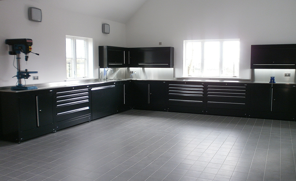 Extensive home workshop area with modular Dura cabinets and porcelain floor tiles